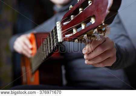 Girl Tunes An Acoustic Guitar Close-up. Playing A Musical Instrument.