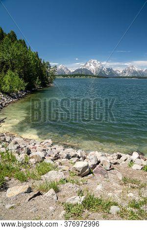 Shores Of Jackson Lake, Near The Jackson Lake Dam In Grand Teton National Park On A Sunny Summer Day