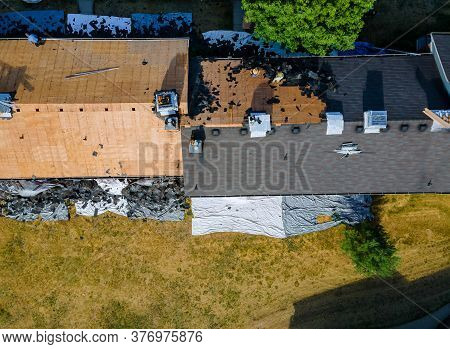 Construction Worker On A Replacement Shingles Roof The House Installed New Shingles Of Residential B