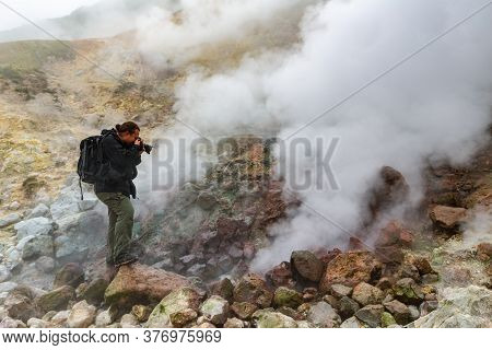 Male Photographer Takes Pictures Of Aggressive Volcanic Landscape, Hot Spring, Eruption Fumarole, Ga