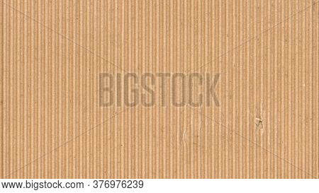 Corrugated cardboard texture. Blank empty cardboard with a single torn hole. Recycled material background.