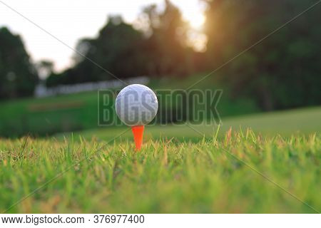Golf Ball On Tee In Beautiful Golf Course With Sunset. Golf Ball Close Up In Golf Coures At Thailand