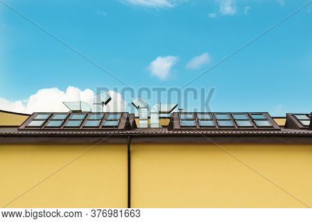 The Roof Of The Yellow Building Against The Blue Sky. Roof Windows And Tin Duct Pipes.