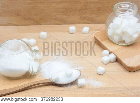 White Sugar And Sugar Cubes In Wood Spoon On Wooden Background With Copy Space