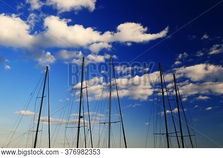 A Number Of Masts Without Sails Standing Near The Shore Yacht, Summer Evening