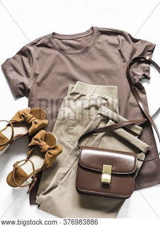 Brown T-shirt, Cotton Joggers Jeans, Suede Brown Sandals, Leather Cross Body Bag On A Light Backgrou