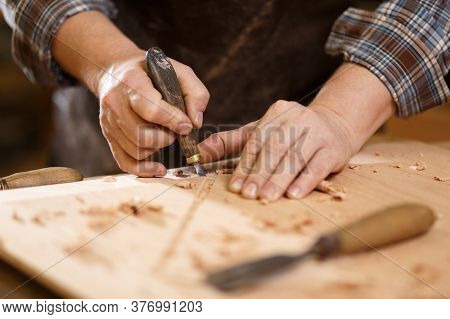 Carpenter With Chisel In The Hands On The Workbench. Vintage