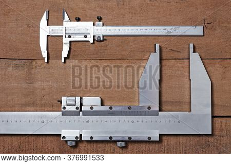 Carpenter Tools On The Wood Table Background. Big And Small Vernier Caliper.