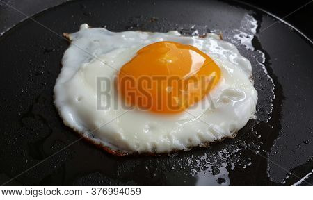 Yummy Fried Egg On A Black Surface . Food Close Up.