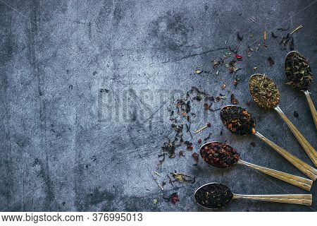 Various Types Of Herbal Tea In Spoons. Spoons With Dry Tea Leaves. Tea On A Concrete Background