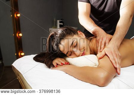 Back Massage. Classical, Therapeutic Massage. Girl On A Back Massage Procedure.