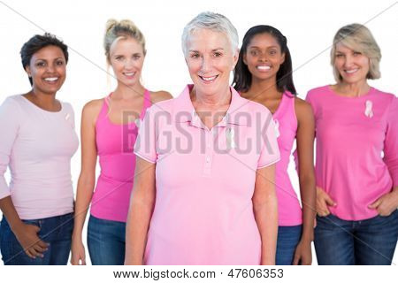 Diverse group of women wearing pink tops and breast cancer ribbons on white background