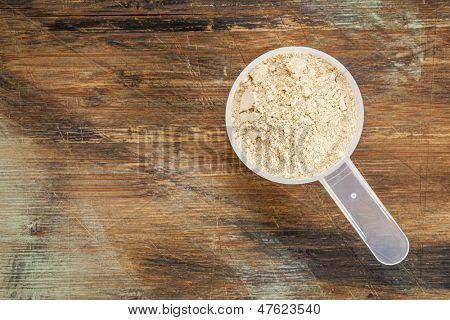 measuring scoop of maca root  powder - top view against painted wood background