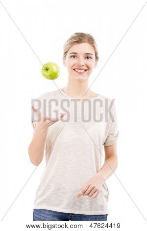 Beautiful girl throwing a green apple into the air, over a white background