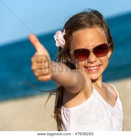 Cute Girl Showing Thumbs Up On Beach.