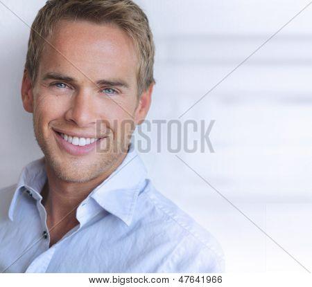 Porträt eines großen schauenden zuversichtlich jungen Mannes mit echten Lächeln