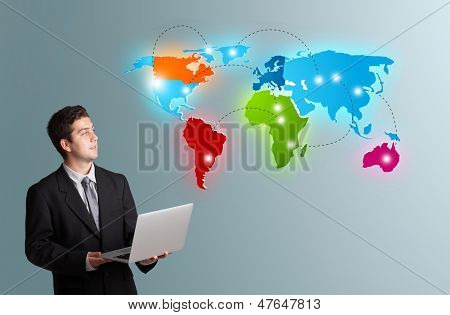 Handsome young man holding a laptop and presenting colorful world map