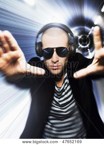 Man wearing headphones and sunglasses with hands out in front of tunnel effect