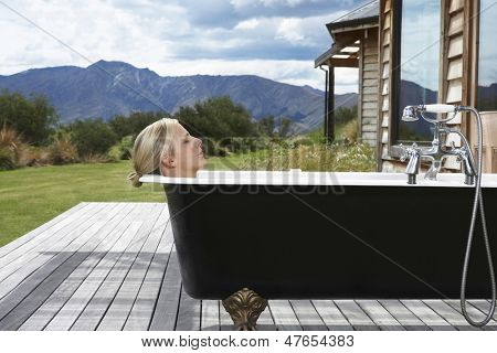 Side view of a young blond woman in bathtub on porch against mountains