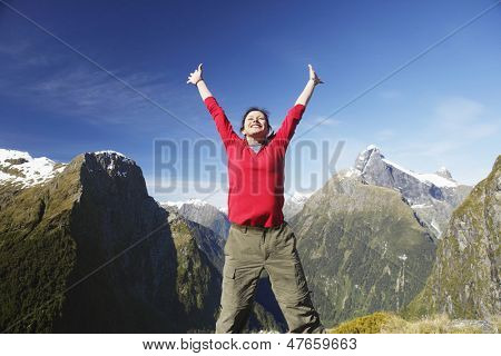 Young happy woman with arms raised against mountain peaks and sky
