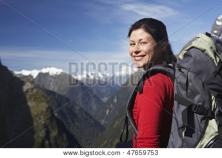 Portrait of a female hiker with backpack against mountain peaks