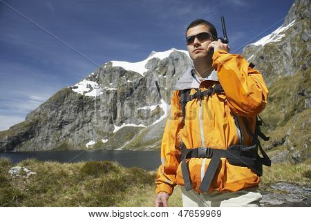 Smart young man using walkie talkie by the lake against mountain
