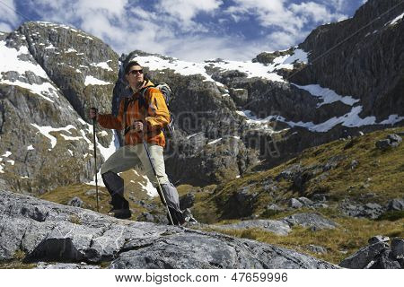 Full length side view of a male hiker with walking sticks in mountains