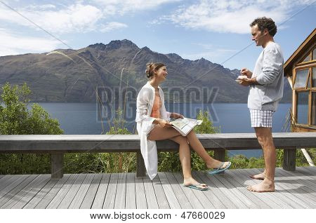 Side view of a couple in pajamas on balcony overlooking a mountain lake