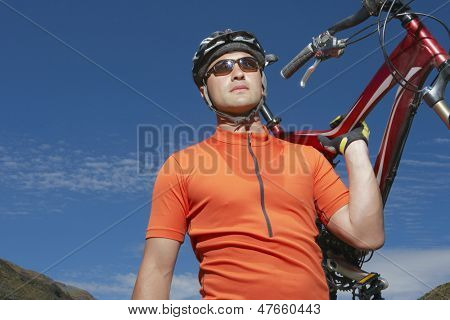Male cyclist carrying bike against blue sky
