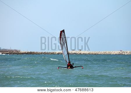 Small trimaran with sail preparing to go to sea in the hot summer day on the beach poster