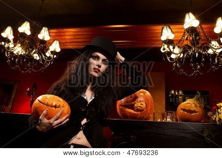 Halloween concept: sexy lady vampire next to bar over red background