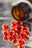 Closeup of orange vitamin pills and pill bottle poster