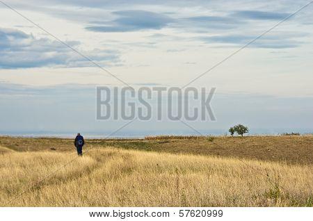 Lonely hiker is walking through flat prarie terrain