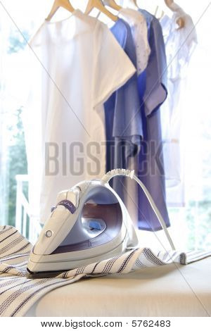 Iron On Ironing Board With Clothes Hanging