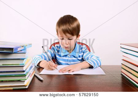 little boy sits at his desk and carefully writing in exercise book. boy 5 years. on the desk a lot of books. photo taken on a light background poster