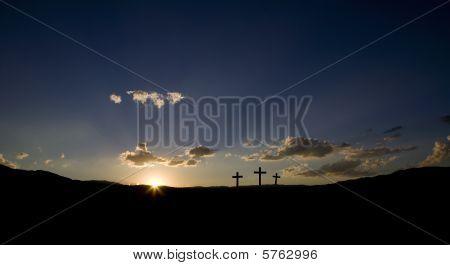 Three empty Roman crosses at sunrise or sunset