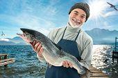Fisherman holding a big atlantic salmon fish in the fishing harbor poster