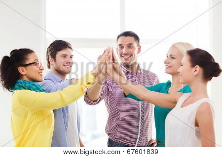 business, office, gesture and startup concept - smiling creative team doing high five gesture in office poster