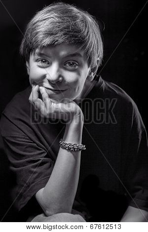 Black And White Portrait Of A Smiling Male Teenager With Black Background