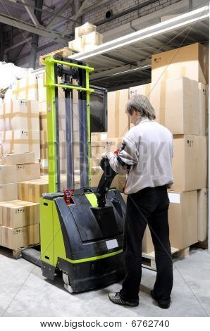 Operator Of Electric Forklift Stacker In Warehouse
