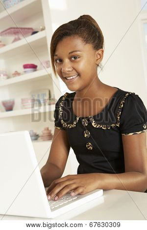 Pre-teen girl working on laptop at home