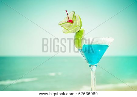 Blue Margarita Cocktail With Lime Fruit And Cherry Decoration At Tropical Ocean Beach