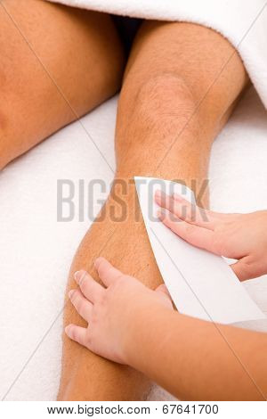Close-up Of Therapist Waxing Man's Leg