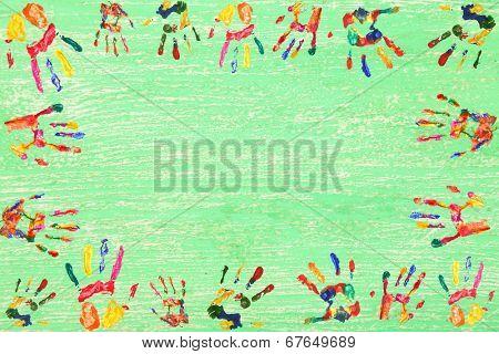 Frame of color hands print on wooden background