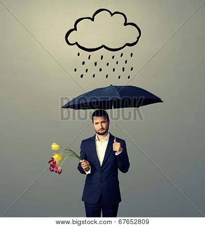 sad young man with black umbrella and drooped flowers standing under drawing storm cloud. photo over grey background