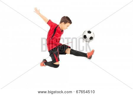 Junior football player kicking a ball isolated on white background