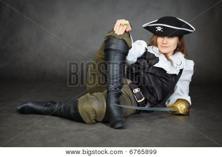 Iimpudent Woman Pirate Lies With Sabre On Black Background