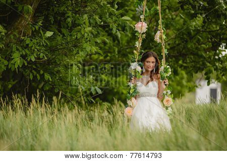 Beautiful bride rides a swing in the park.