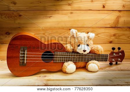 Ukulele On Wood Background.