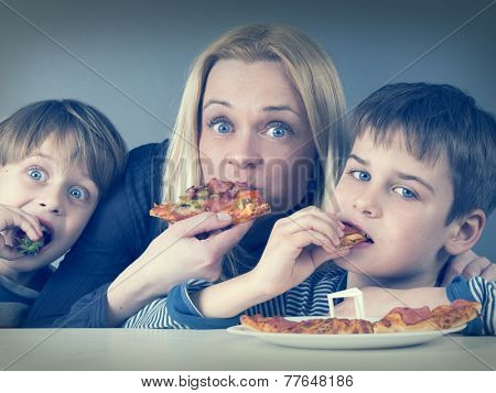 Hungry mother and kids, eating pizza together